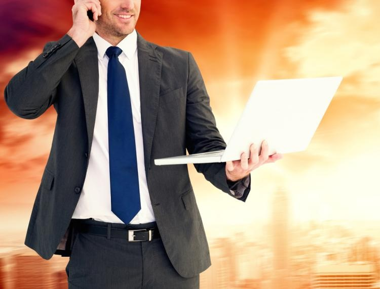 business man holding laptop whilst on the phone